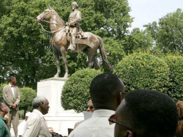Protesters attend a rally protesting against the name of Nathan Bedford Forrest Park in front of a statue bearing his likeness August 13, 2005 in Memphis, Tennessee. Nathan Bedford Forrest was a Civil War General who led troops against the north. Forrest was originally buried in Elmwood Cemetery in Memphis. …