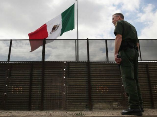 U.S. Border Patrol agent Jerry Conlin stands on the American side of the U.S.-Mexico border fence on October 3, 2013 at San Ysidro, California. While hundreds of thousands of government workers were furloughed due to the federal shutdown, thousands of Border Patrol agents, air-traffic controllers, prison guards and other federal …