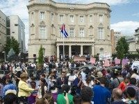 Members of the media and onlookers watch the raising of the Cuban flag over their new embassy in Washington, DC July 20, 2015. Cuba's blue, red and white-starred flag was hoisted Monday at the country's embassy in Washington in a symbolic move signaling the start of a new post-Cold War …