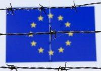 A barbed wire is seen in front of a European Union flag at an immigration reception centre in Bicske