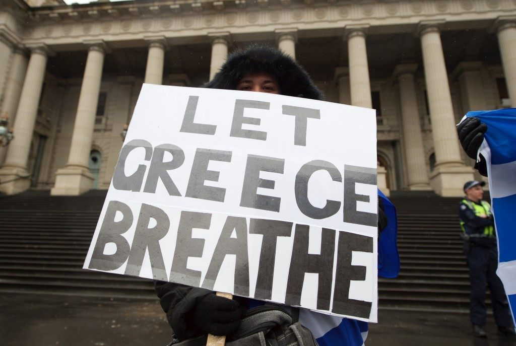 A protestor holds a banner at a Greece solidarity rally outside Parliament House in Melbourne, Australia. THEO KARANIKOS/AFP/Getty Images
