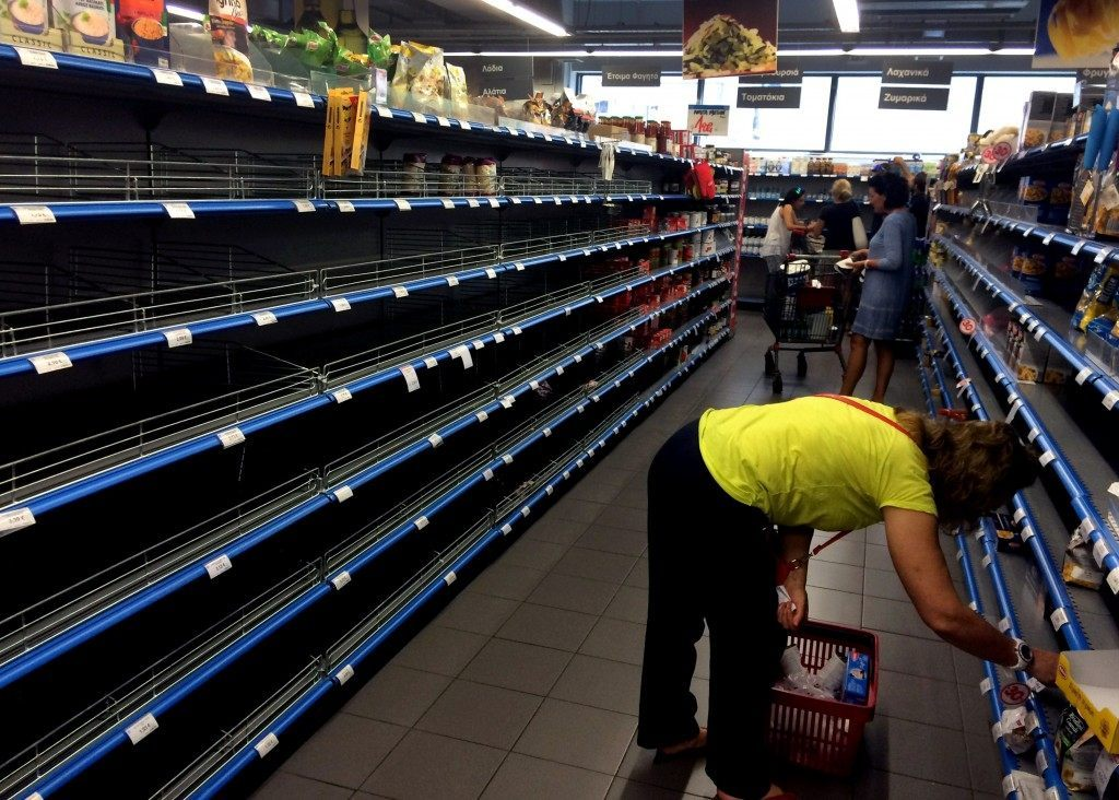 Shoppers stand in a supermarket aisle with empty shelves as food supplies run low. ARIS MESSINIS/AFP/Getty Images