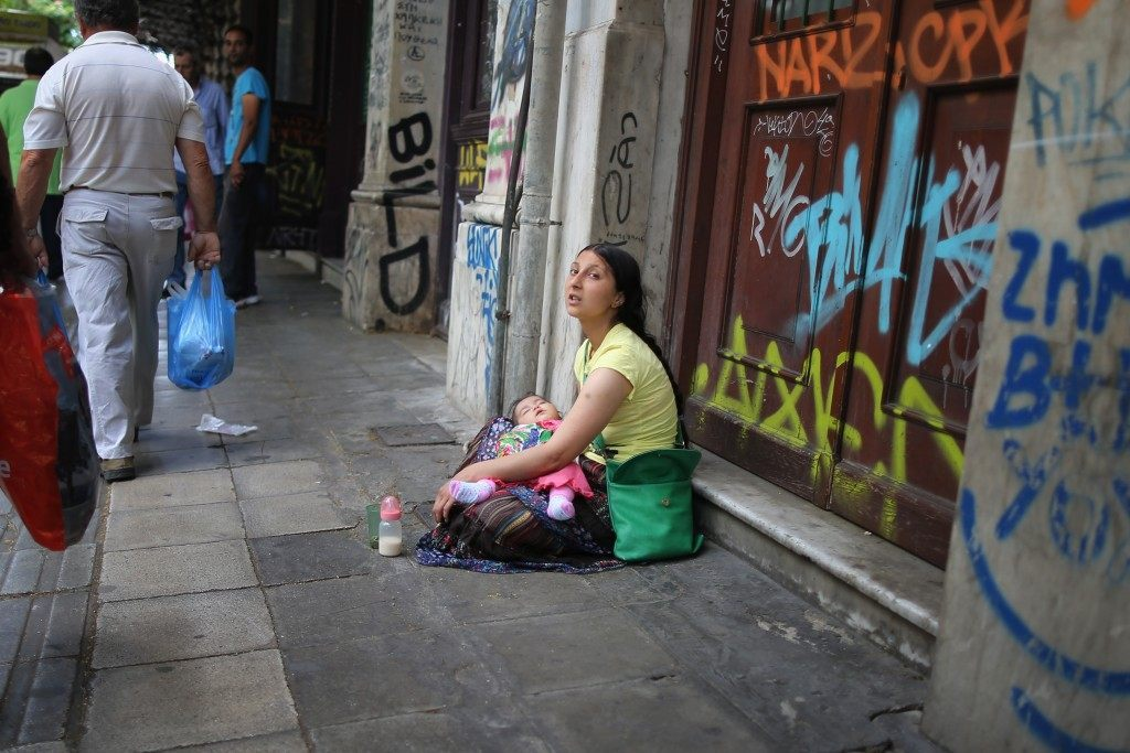 A woman begs on an Athens street on the eve of Greece's austerity vote. CHRISTOPHER FURLONG/Getty Images