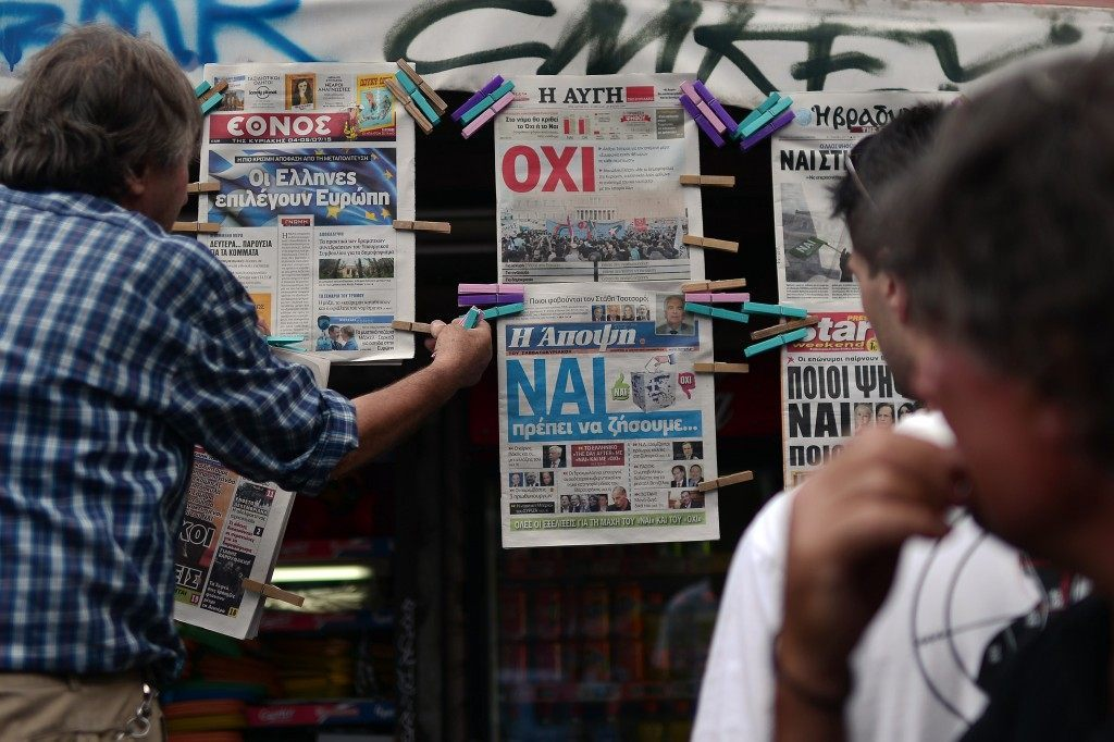 "A newsagent hangs newspapers bearing ""No"" and ""Yes"" headlines in central Athens. LOUISA GOULIAMAKI/AFP/Getty Images"