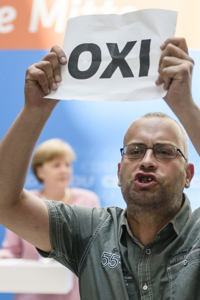 A protester holds a sheet with the Greek word for 'No' during an open house presentation of Germany's conservative Christian Democratic Union (CDU) while German Chancellor Angela Merkel speaks in the background. AFP PHOTO / CLEMENS BILAN
