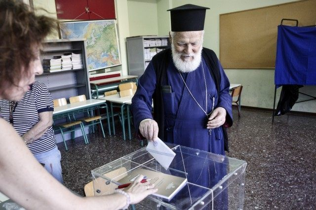 ATHENS, GREECE - JULY 5: An Orthodox priest puts a referendum vote in the ballot box at a school on July 5, 2015 in Athens, Greece. The people of Greece are going to the polls to decide if the country should accept the terms and conditions of a bailout with …