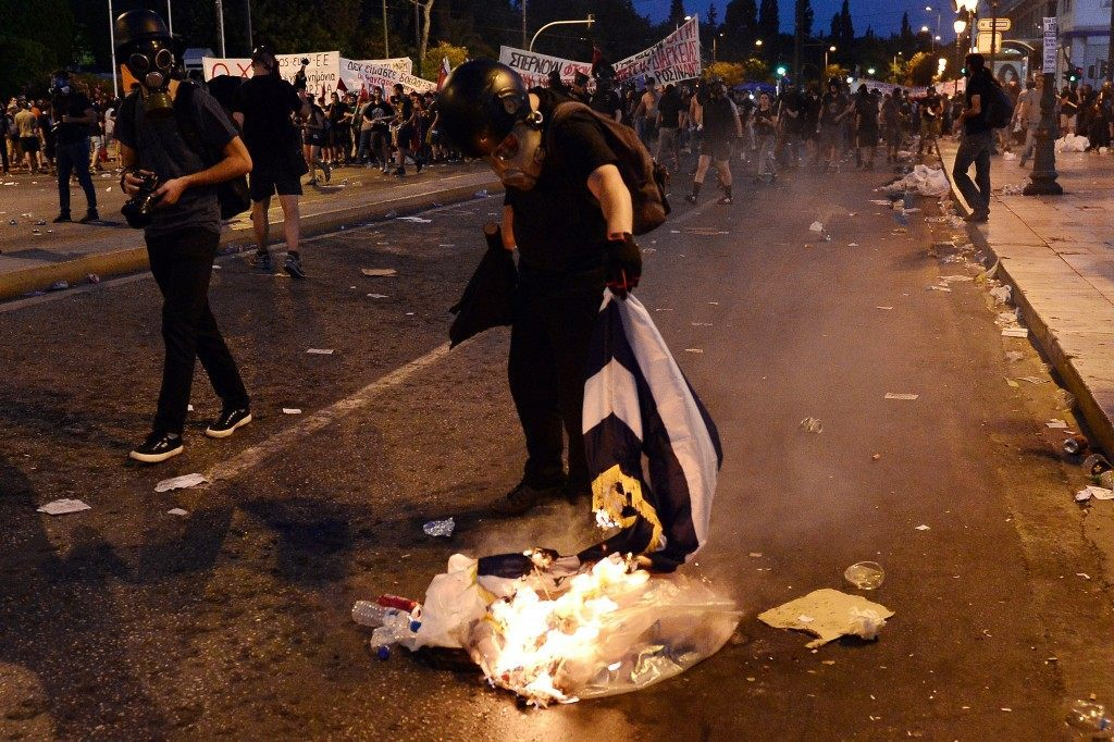 A protester burns a Greek flag (LOUISA GOULIAMAKI/AFP/Getty Images)