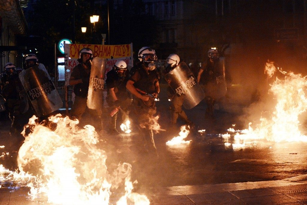 Riot police stand amid petrol bombs thrown by protesters. (LOUISA GOULIAMAKI/AFP/Getty Images)