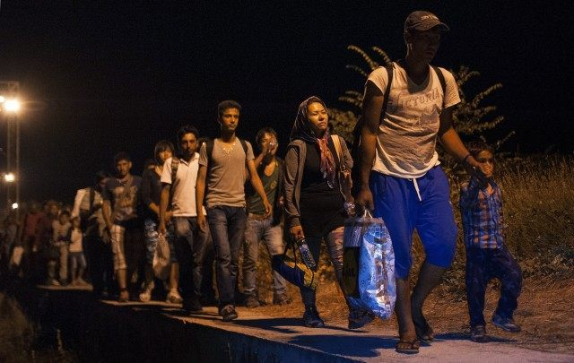 Migrants walk on train tracks (ROBERT ATANASOVSKI/AFP/Getty Images)