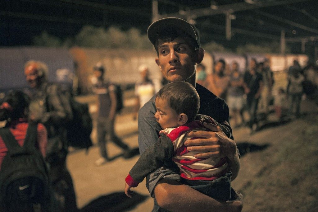 A migrant holds his child as he leaves a train at a railway station on the Tabanovce border crossing between Macedonia and Serbia on July 16, 2015 (ROBERT ATANASOVSKI/AFP/Getty Images)