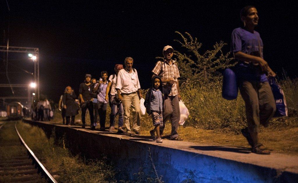 Migrants walk near train tracks at the border crossing (ROBERT ATANASOVSKI/AFP/Getty Images)