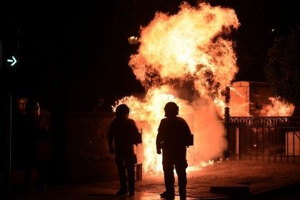A fire bomb explodes behind riot police (ARIS MESSINIS/AFP/Getty Images)