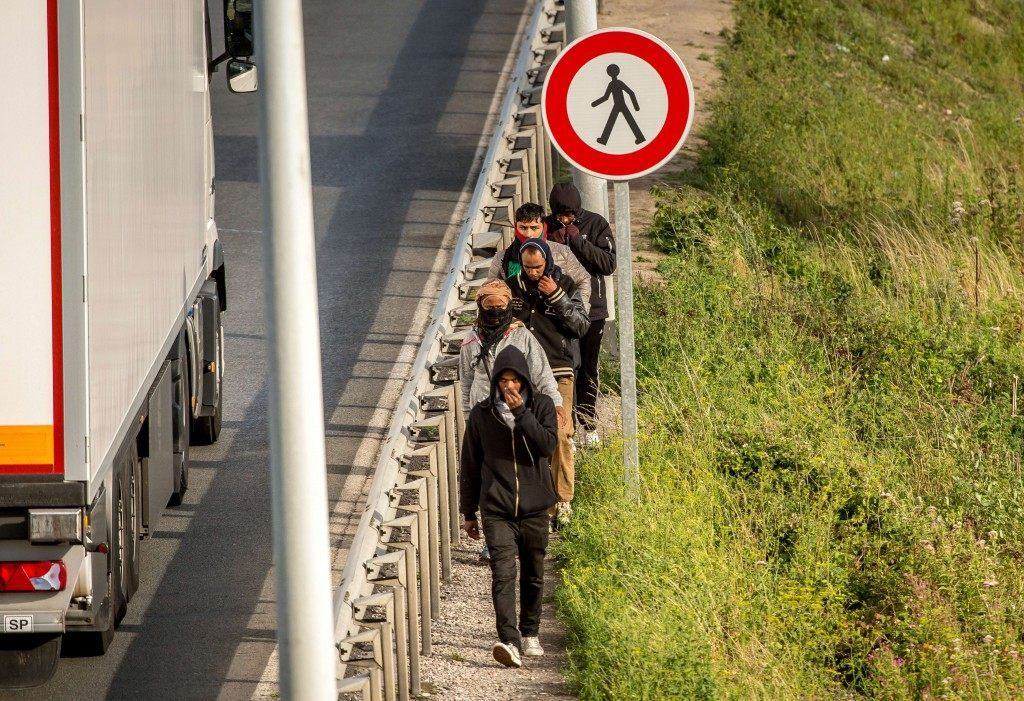 Migrants walk alongside vehicles on the route leading to the Channel Tunnel in Coquelles (PHILIPPE HUGUEN/AFP/Getty Images)