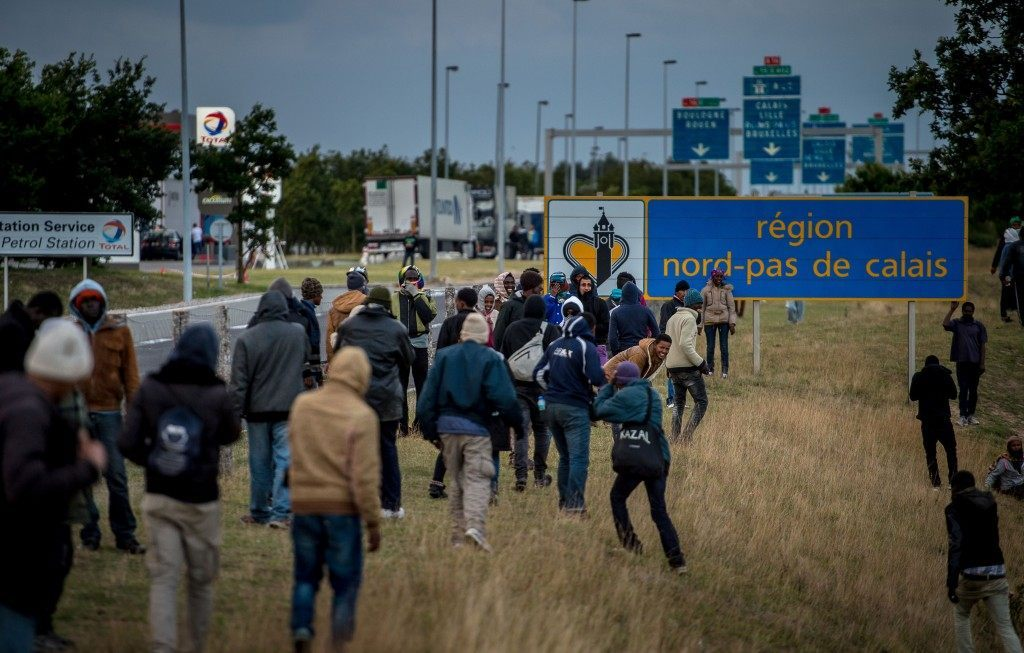 Migrants walk in the direction of the Channel Tunnel (PHILIPPE HUGUEN/AFP/Getty Images)