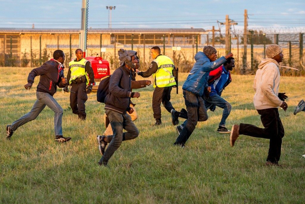 Migrants trying to reach the Channel Tunnel run past policemen (PHILIPPE HUGUEN/AFP/Getty Images)