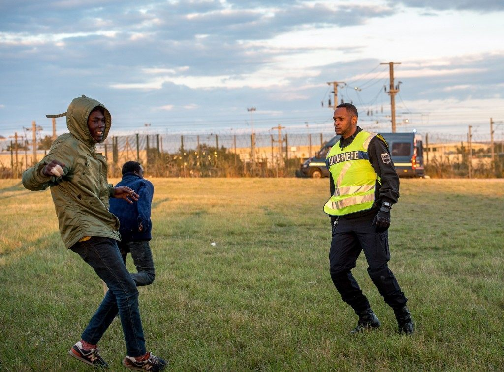 A migrant trying to reach the Channel Tunnel faces a policeman (PHILIPPE HUGUEN/AFP/Getty Images)