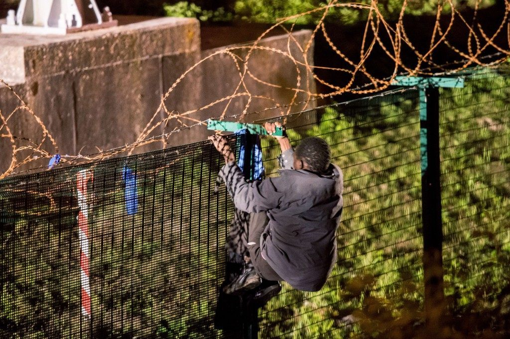 A migrant climbs a security fence (PHILIPPE HUGUEN/AFP/Getty Images)