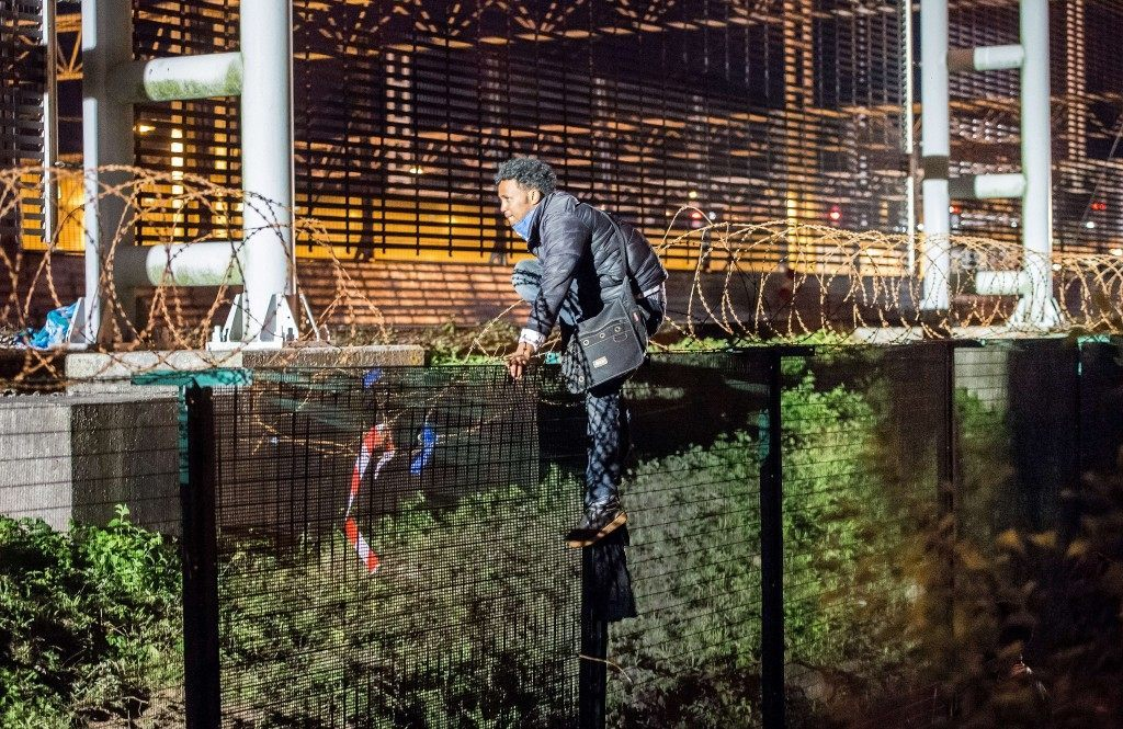 A migrant climbs a security fence of a Eurotunnel terminal in Coquelles near Calais (PHILIPPE HUGUEN/AFP/Getty Images)