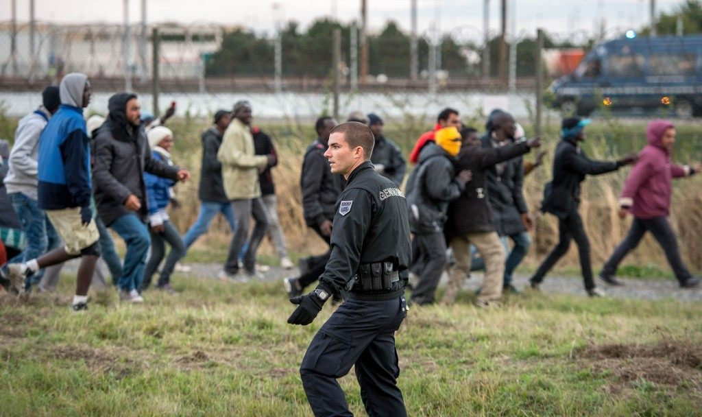 A policeman faces migrants trying to reach the Channel Tunnel (PHILIPPE HUGUEN/AFP/Getty Images)