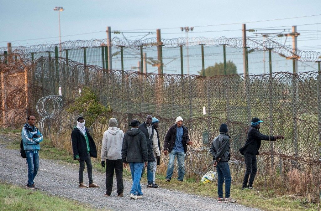 Migrants try to reach the Eurotunnel terminal through a barbed wire fence (PHILIPPE HUGUEN/AFP/Getty Images)