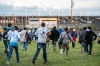 Migrants who managed to pass the police block on the Eurotunnel site run towards the boarding docks (PHILIPPE HUGUEN/AFP/Getty Images)