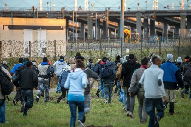 Migrants who managed to pass the police block on the Eurotunnel site run towards the boarding docks in Coquelles near Calais (PHILIPPE HUGUEN/AFP/Getty Images)