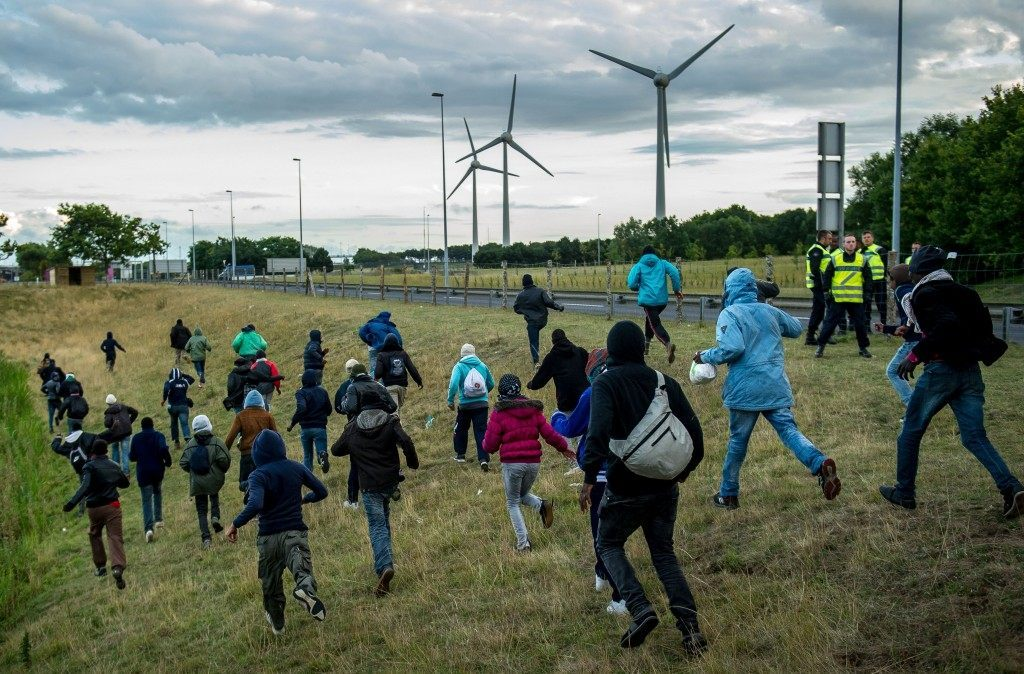 Migrants who managed to pass the police block on the Eurotunnel site make their way towards the boarding docks (PHILIPPE HUGUEN/AFP/Getty Images)