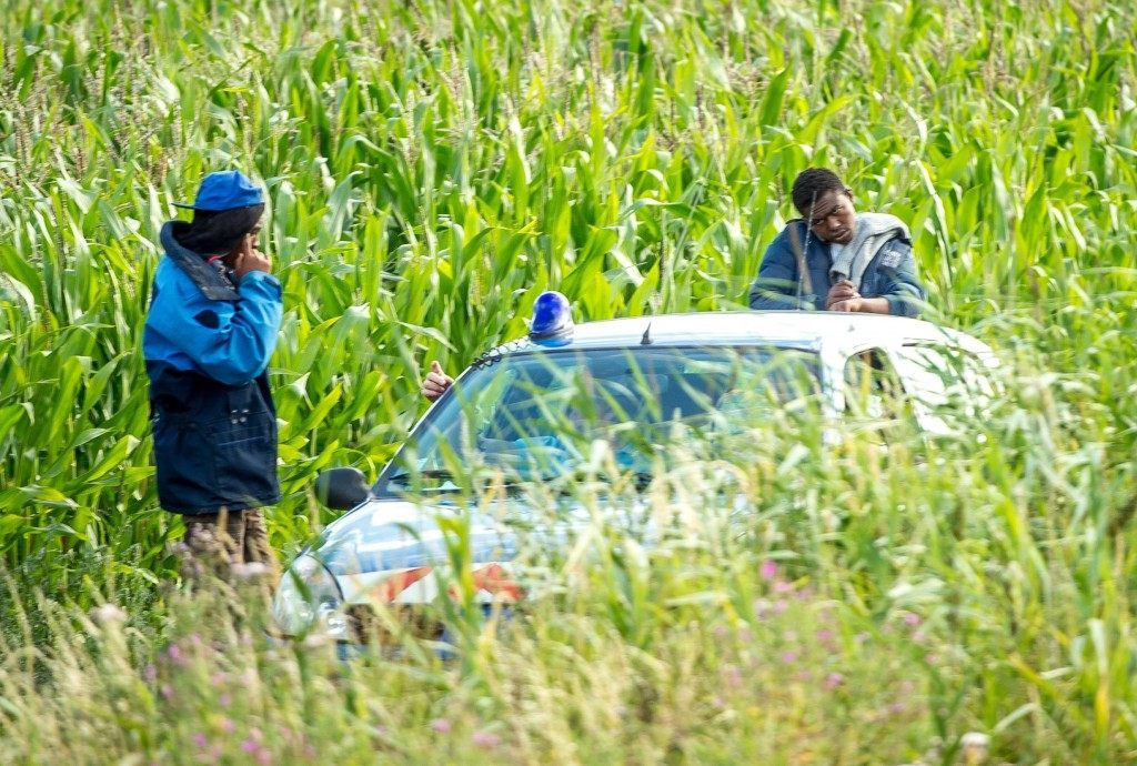 French gendarmes accompany two migrants through a field near the Eurotunnel site (PHILIPPE HUGUEN/AFP/Getty Images)