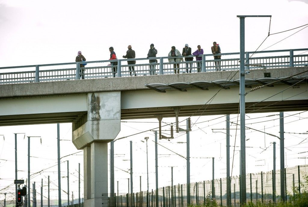 Migrants stand on a bridge near the Eurotunnel site (PHILIPPE HUGUEN/AFP/Getty Images)