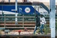 Migrants walk on the tracks in the Eurotunnel site (PHILIPPE HUGUEN/AFP/Getty Images)