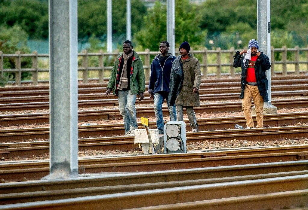 Migrants walk on the tracks in the Eurotunnel site in Frethun near Calais (PHILIPPE HUGUEN/AFP/Getty Images)