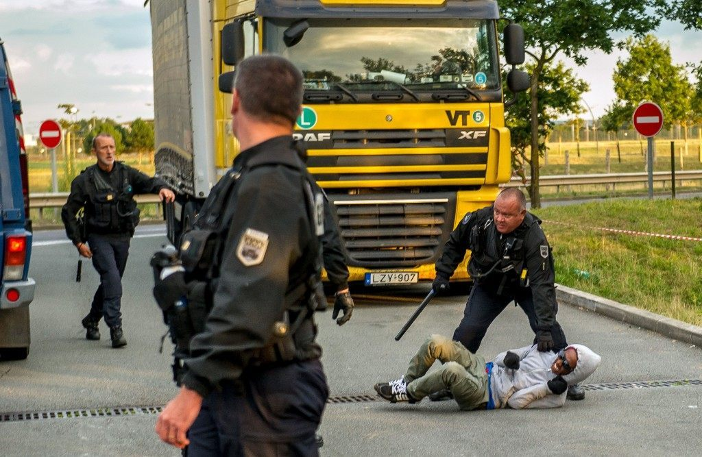 French gendarmes attempt to block a migrant after he entered the Eurotunnel site (PHILIPPE HUGUEN/AFP/Getty Images)