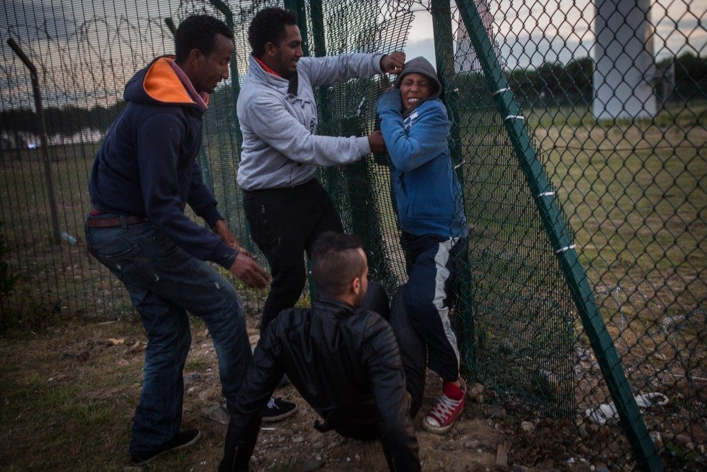 People help a young man squeeze through a gap in a fence (Rob Stothard/Getty Images)