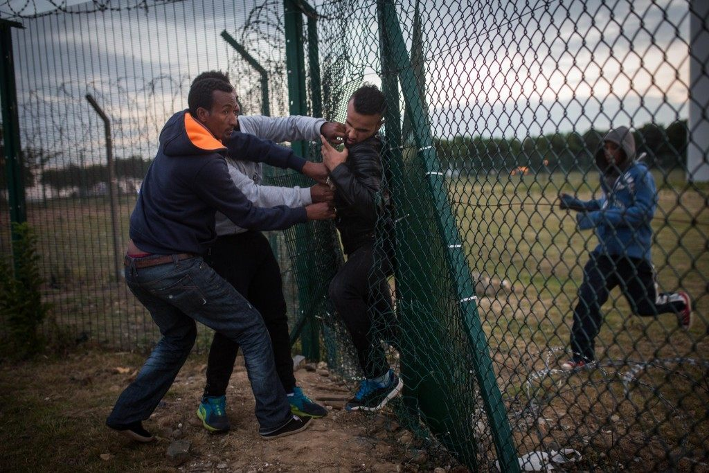 Migrants help a man squeeze through a gap in a fence (Rob Stothard/Getty Images)