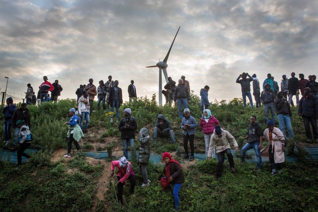 Migrants walk down a slope beside a road leading to the Eurotunnel terminal (Rob Stothard/Getty Images)