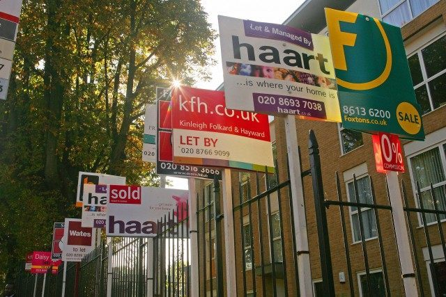Property sale boards are pictured in For