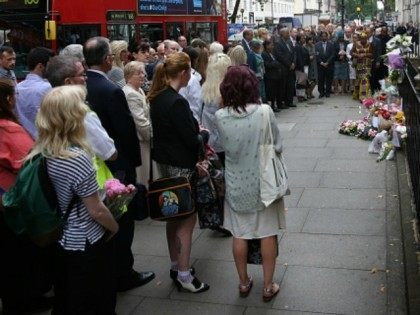 Buses pass by as family members attend a remembrance ceremony at the spot where 13 people were killed in the London bombings on July 7, 2015 in London, England.Today is the tenth anniversary of the 7/7 bombings, when four suicide bombers struck transport system in central London on Thursday 7 …