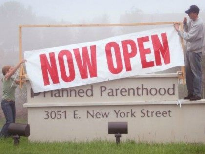 Workers at a Planned Parenthood clinic hang a banner to announce the opening of the facility October 2, 2007 in Aurora, Illinois. The clinic, reported to be the largest Planned Parenthood clinic in the country, was scheduled to open last month but the opening was held up by last minute …