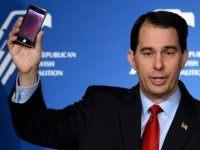 Wisconsin Gov. Scott Walker holds up his cell phone as he speaks during the Republican Jewish Coalition spring leadership meeting at The Venetian Las Vegas on March 29, 2014 in Las Vegas, Nevada. The Republican Jewish Coalition began its annual meeting with potential Republican presidential candidates in attendance, along with …