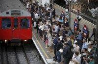 Commuters at Earls Court underground station, awaiting the arrival of a train, attempt to complete their journey on Wednesday evening, in London