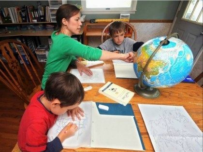 In this Aug. 24, 2012 photo, Elizabeth Boggs works with her sons Nathan, right, and Luke, left, with mapping and geography at her home in Charleston, Ill. Boggs is a member of the East Central Illinois Home Educator's Network, a homeschool support group with more than 40 member families. (AP …