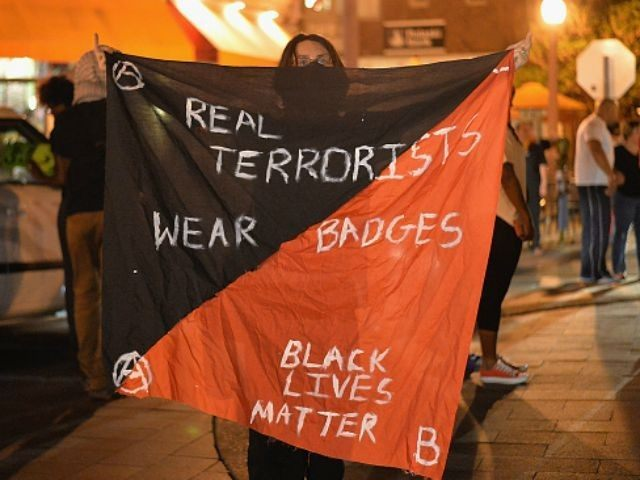 A woman holds a banner during a protest action through the Central West End of St. Louis, Missouri on August 20, 2015. After a night of unrest sparked by a police involved shooting, demonstrators took to the streets in actions of civil disobedience. (Photo by