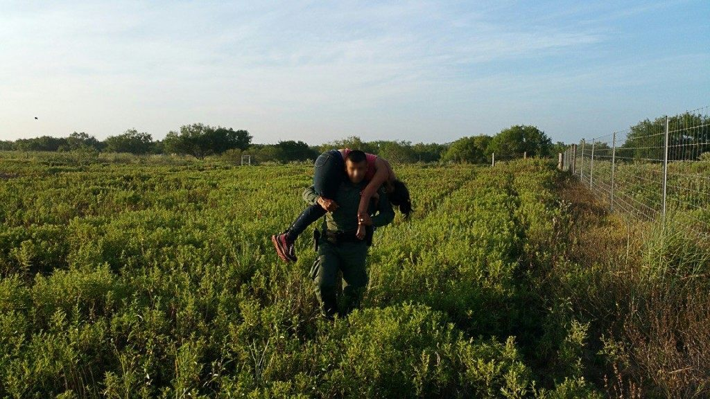 U.S Border Patrol agent carries to safety a woman who had been abandoned by a human smuggler