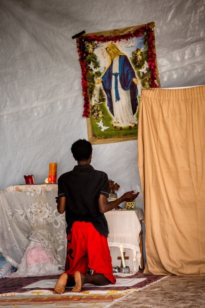 A migrant offers prayers at the makeshift church (PHILIPPE HUGUEN/AFP/Getty Images)
