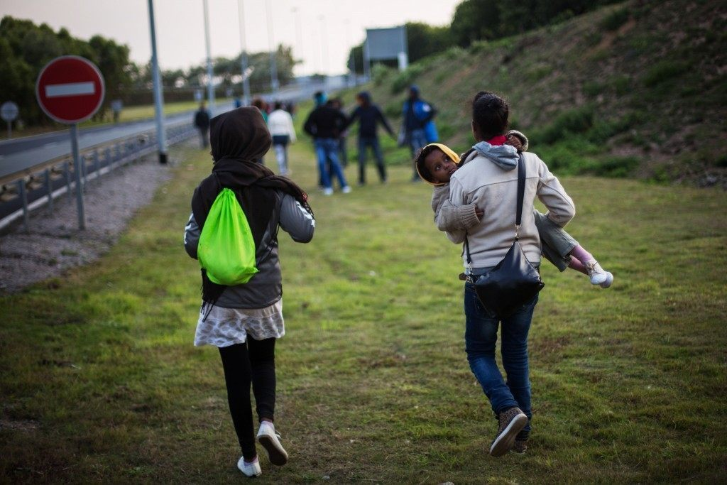 A woman carries a child as they walk towards the Eurotunnel terminal (Rob Stothard/Getty Images)