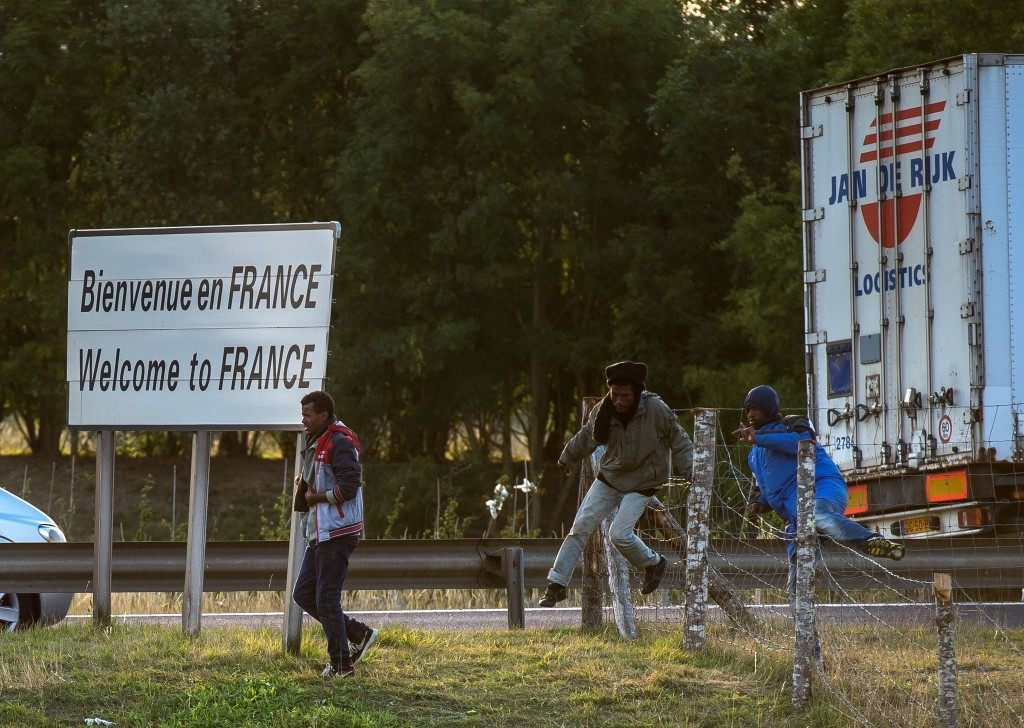 Migrants who managed to get past roadblocks set up by French gendarmes inside the Eurotunnel site run to the boarding platform to attempt to reach Britain (PHILIPPE HUGUEN/AFP/Getty Images)