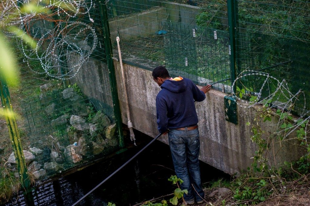 A migrant who managed to get past roadblocks set up by French gendarmes inside the Eurotunnel site, tries to find a way to cross the fences topped with barbed wire which protect the boarding platform. (PHILIPPE HUGUEN/AFP/Getty Images)