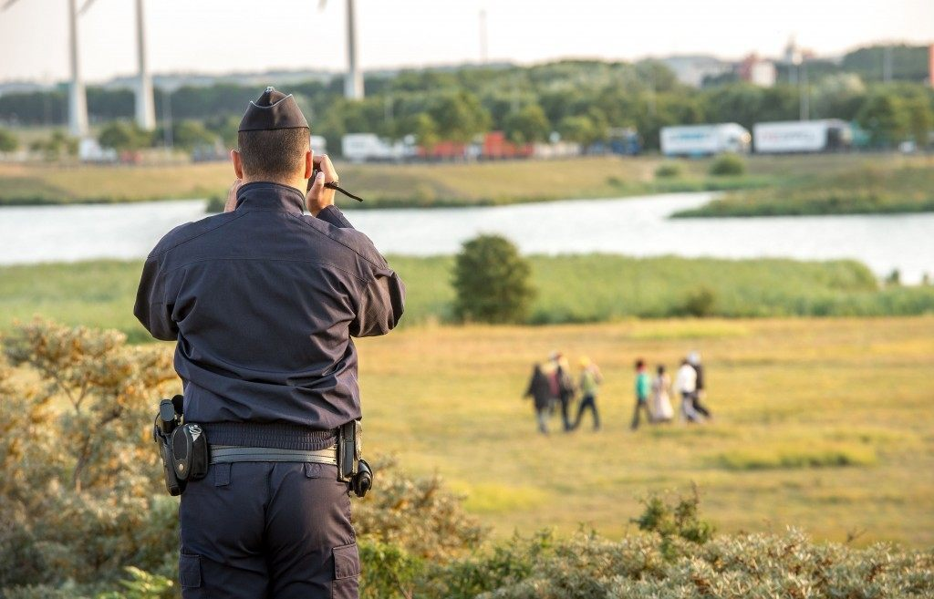 A French gendarme films the migrants who try to enter inside the Eurotunnel site (PHILIPPE HUGUEN/AFP/Getty Images)
