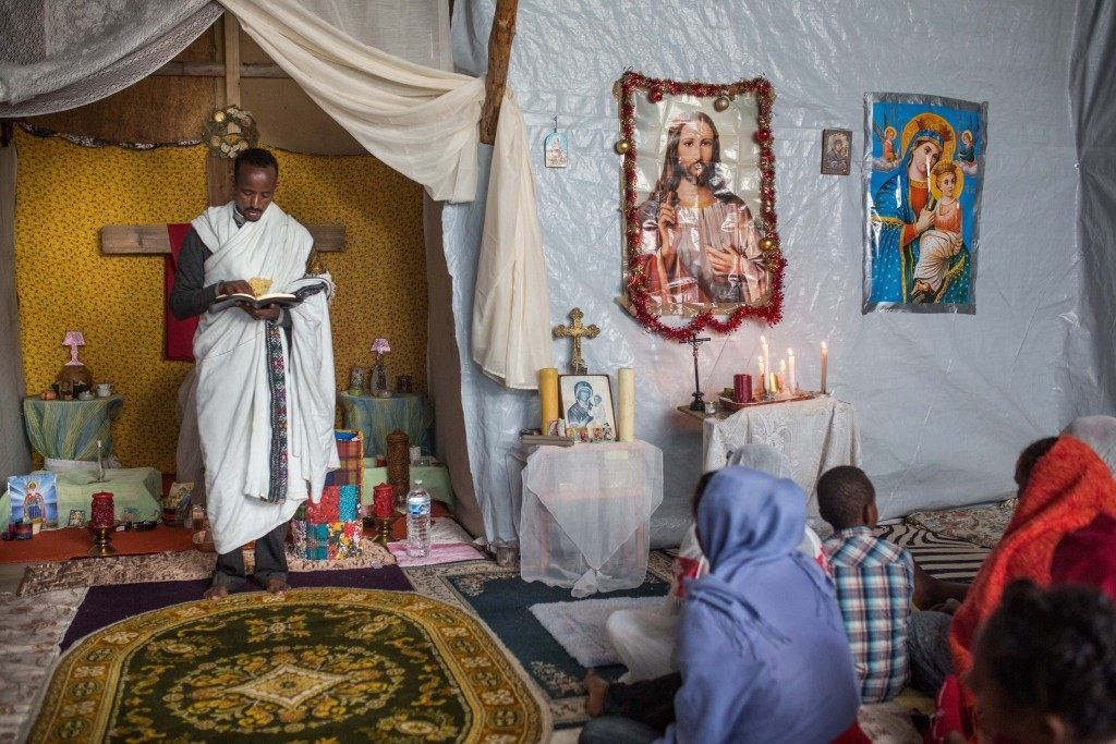 Kibrom Kasta leads an Orthodox service for Ethiopian and Eritrean worshippers at a make shift church. (Rob Stothard/Getty Images)