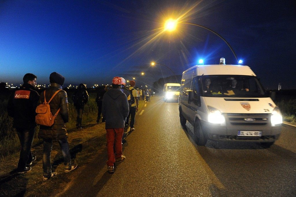 A police vehicle patrols past migrants walking in Coquelles (FRANCOIS LO PRESTI/AFP/Getty Images)